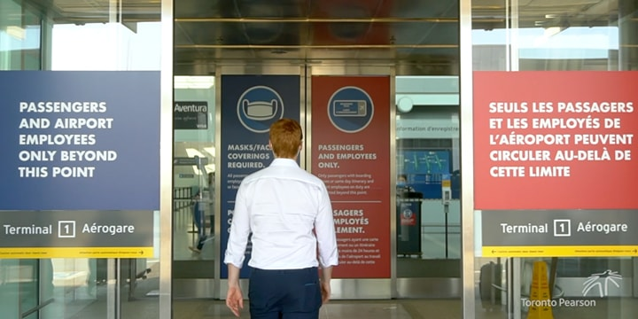 Person entering Pearson Airport through sliding doors with posters on the glass about Healthy Airport