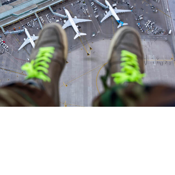 The feet of someone sitting high above airplanes parked at Toronto Pearson Airport