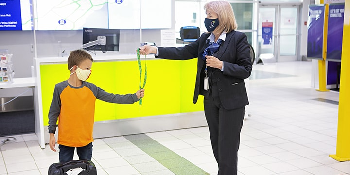 Pearson employee handing a lanyard with a sunflower pattern to a young passenger