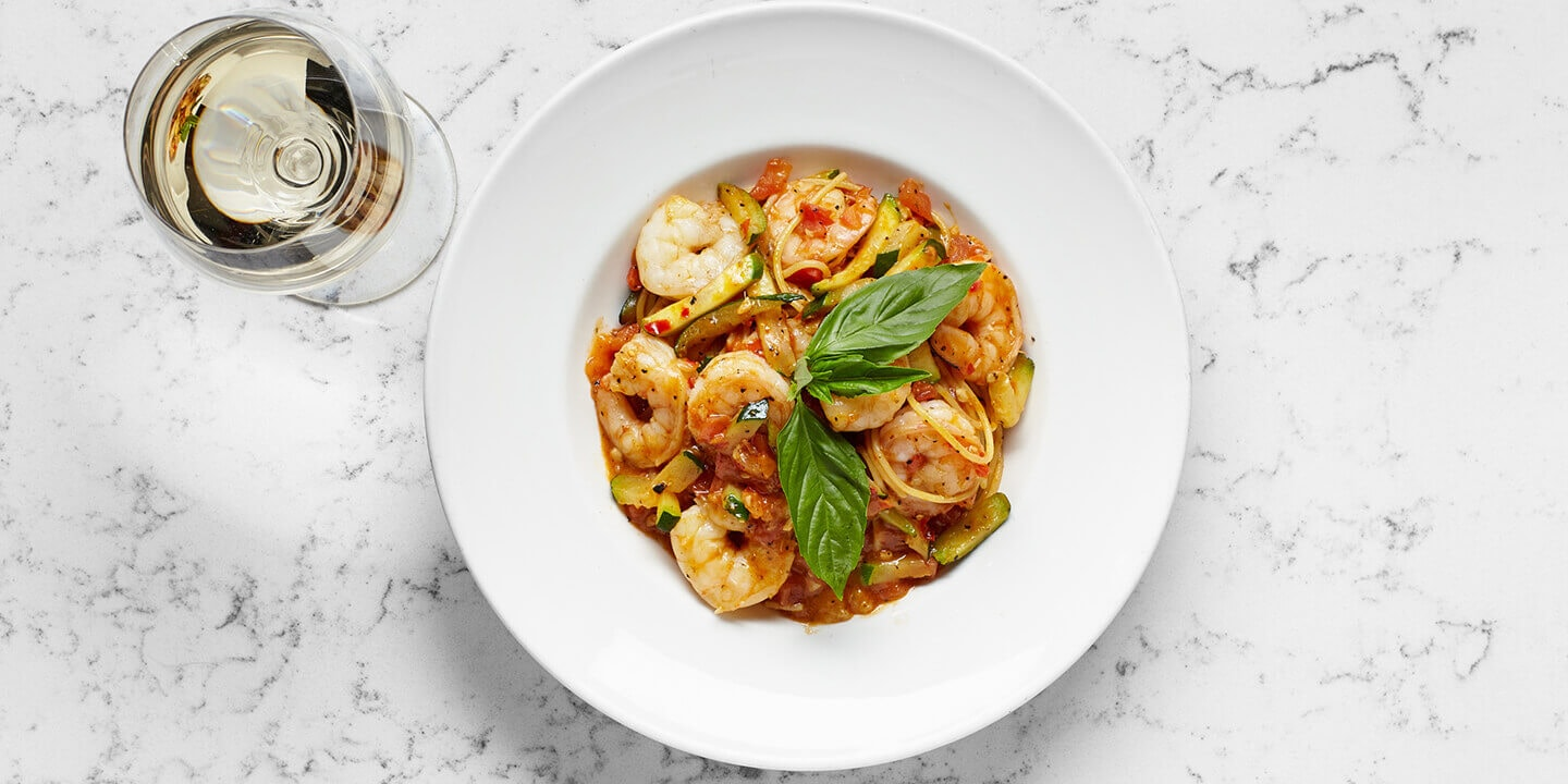 Shrimp on pasta with a glass of white wine