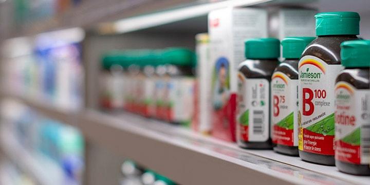 Row of vitamin bottles on pharmacy shelf.