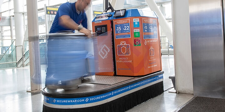 Man wrapping baggage in sheets of blue plastic on Secure Wrap machine